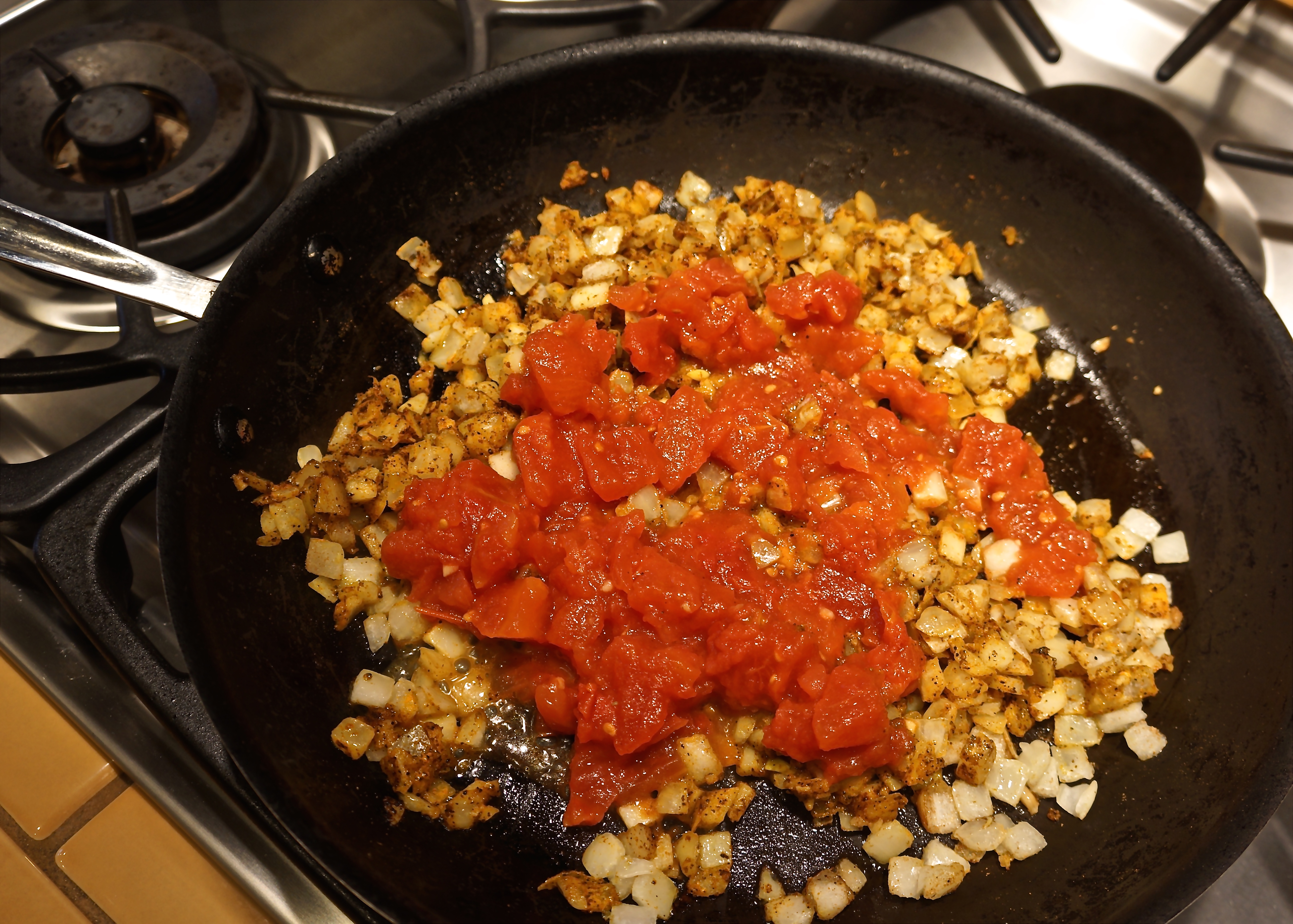 Add chopped tomatoes. Cook stirring until onions are soft.